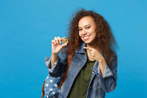 デニムの服を着た若いアフリカ系アメリカ人の女の子の10代の学生、バックパックは青い壁にビットコインを保持
