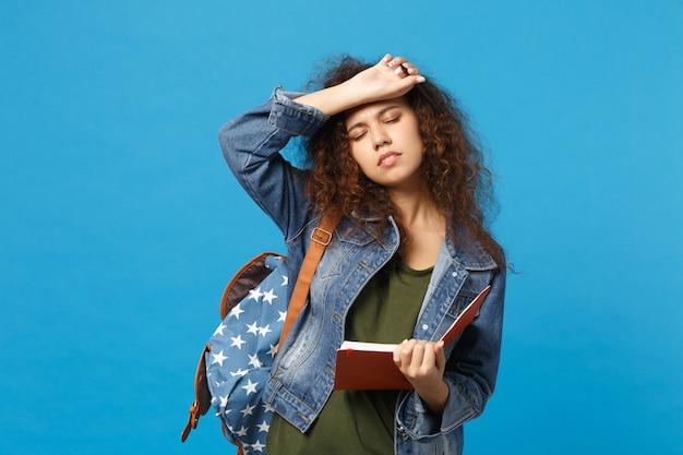 デニムの服を着た若いアフリカ系アメリカ人の女の子の10代の学生、バックパックは青い壁に隔離された本を保持します