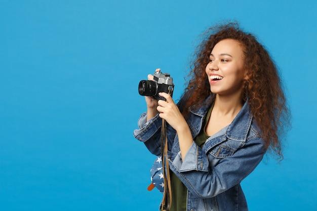 デニムの服のバックパックの若いアフリカ系アメリカ人の女の子の十代の学生は、青い壁に分離されたカメラを保持します