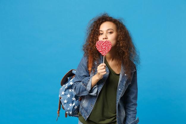 デニムの服を着た若いアフリカ系アメリカ人の女の子の十代の学生、バックパックは青い壁に隔離されたキャンディーを保持します