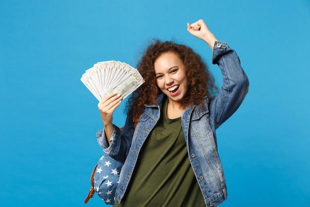 Молодая афро-американская девушка-подросток-студент в джинсовой одежде, рюкзак держит наличные деньги, изолированные на синей стене