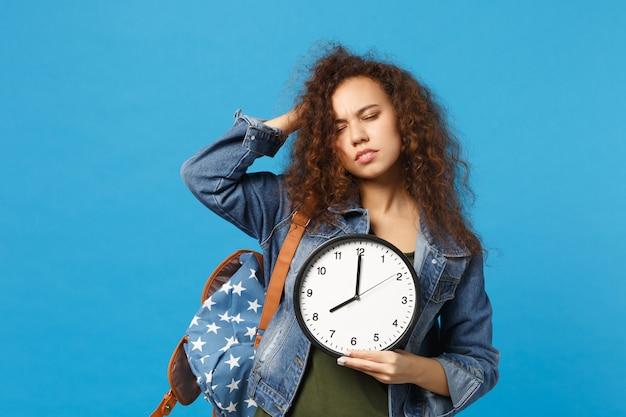 데님 옷에 젊은 아프리카 계 미국인 여자 십대 학생, 배낭 보류 시계 파란색 벽에 고립