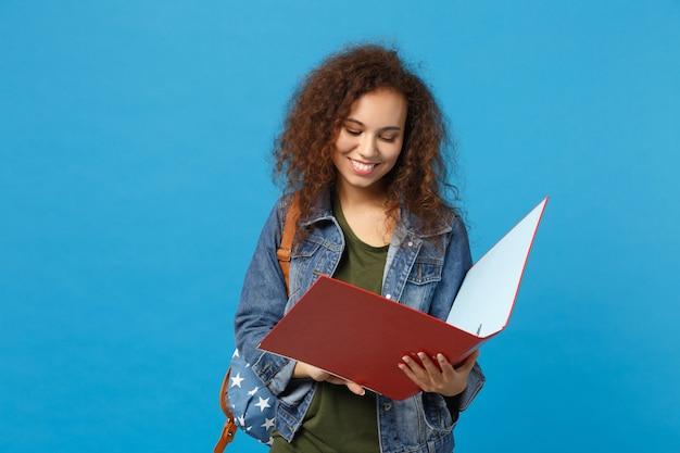 デニムの服のバックパックの若いアフリカ系アメリカ人の女の子の十代の学生は、青い壁に分離されたフォルダーを保持します