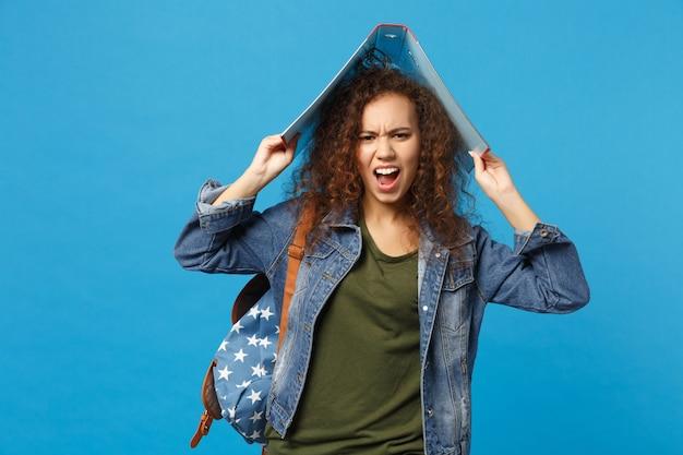 데님 옷 배낭에 젊은 아프리카 계 미국인 여자 십대 학생 파란색 벽에 고립 된 폴더를 개최