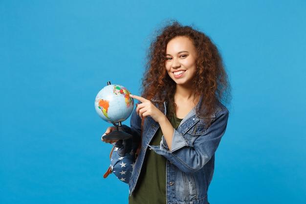 Молодая афро-американская девушка-подросток-студент в джинсовой одежде, рюкзак держит глобус, изолированный на синей стене