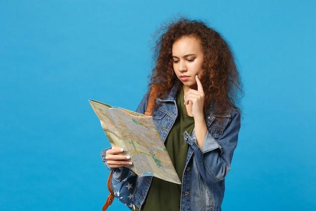 デニムの服を着た若いアフリカ系アメリカ人の女の子の十代の学生、青い壁に隔離されたバックパック保持地図