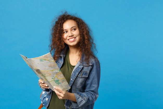 Молодая афро-американская девушка-подросток-студент в джинсовой одежде, рюкзак держит карту, изолированную на синей стене