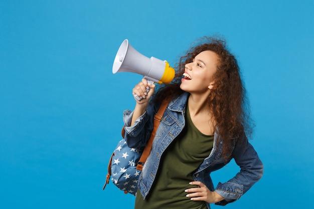 デニムの服を着た若いアフリカ系アメリカ人の女の子の10代の学生、青い壁に隔離されたバックパック保持メガホン