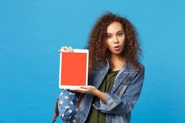 Молодая афро-американская девушка-подросток-студент в джинсовой одежде, рюкзак для удерживания пк изолирован на синей стене