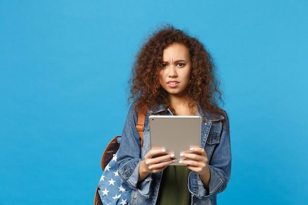デニムの服を着た若いアフリカ系アメリカ人の女の子の10代の学生、青い壁に隔離されたバックパックホールドパッドpc