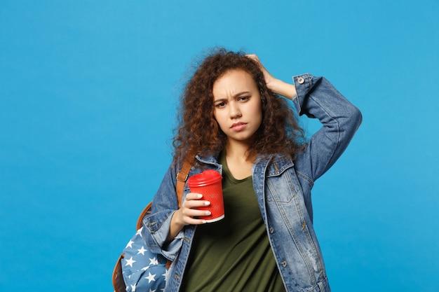 デニムの服を着た若いアフリカ系アメリカ人の女の子の10代の学生、青い壁に隔離されたバックパック保持紙コップ