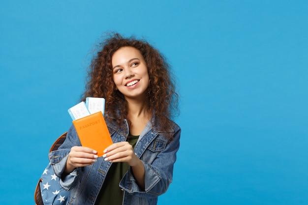 デニムの服を着た若いアフリカ系アメリカ人の女の子の十代の学生、青い壁に隔離されたバックパックホールドパス