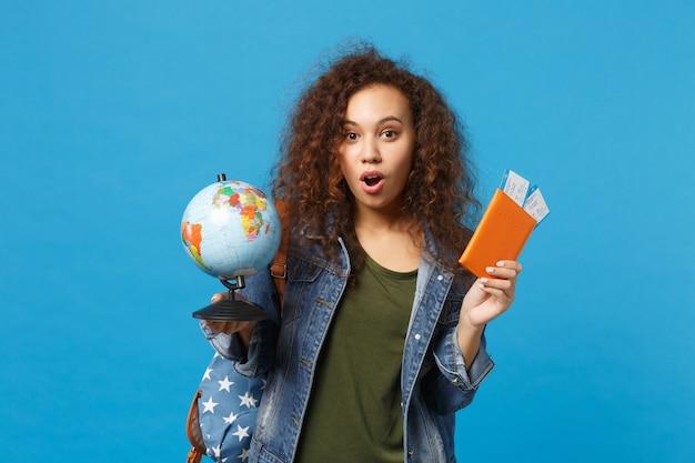 Молодая афро-американская девушка-подросток студент в джинсовой одежде, рюкзак держит пропуск, изолированный на синей стене