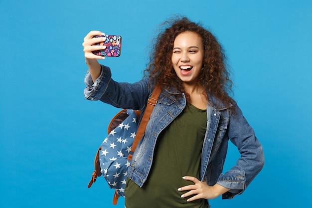 デニムの服を着た若いアフリカ系アメリカ人の女の子の十代の学生、青い壁に隔離されたバックパック保持電話