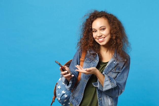 Молодая афро-американская девушка-подросток-студент в джинсовой одежде, рюкзак держит телефон, изолированный на синей стене