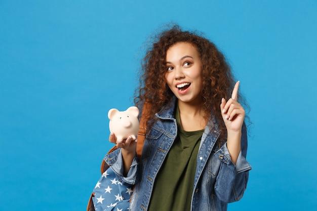 Молодая афро-американская девушка-подросток студент в джинсовой одежде, рюкзак держит свинью, изолированную на синей стене