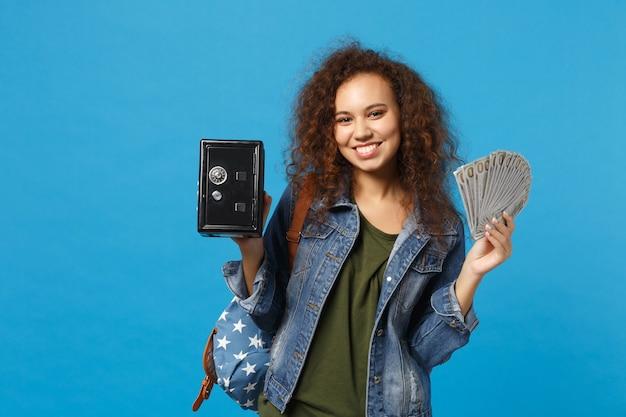 Молодая афро-американская девушка-подросток-студент в джинсовой одежде, рюкзак держит сейф, изолированный на синей стене