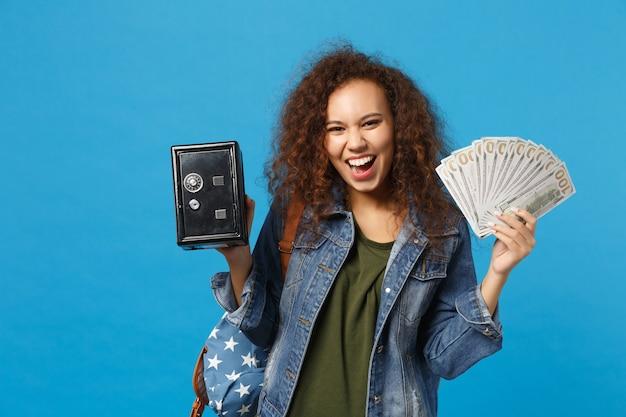 デニムの服を着た若いアフリカ系アメリカ人の女の子の十代の学生、青い壁に隔離されたバックパック保持金庫