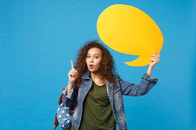 데님 옷을 입은 젊은 아프리카 계 미국인 여자 십대 학생, 배낭 보류 파란색 벽에 고립 된 구름 말