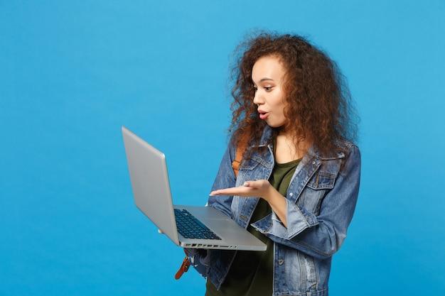 데님 옷에 젊은 아프리카 계 미국인 여자 십대 학생, 파란색 벽에 고립 된 pc에서 배낭 작업