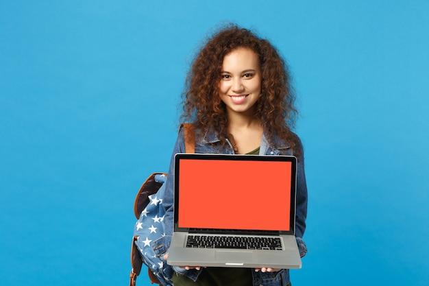 Молодая афро-американская девушка-подросток-студент в джинсовой одежде, рюкзак работает на пк, изолированном на синей стене