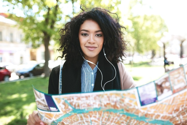 Young african american girl walking around city with map