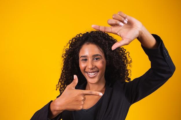 Молодая афро-американская девушка в исполнительной одежде улыбается, делая фоторамку руками и пальцами с счастливым лицом. концепция творчества и фотографии.