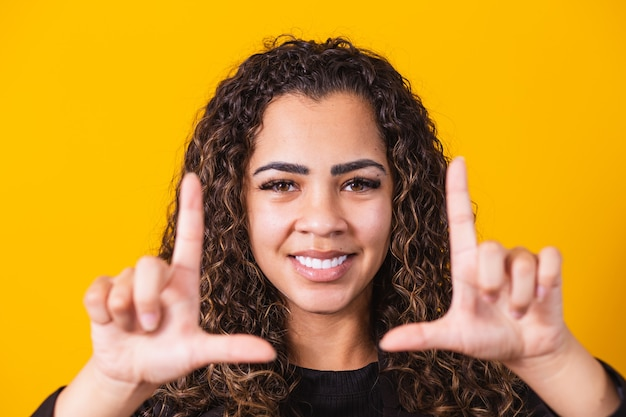 Young african american girl wearing executive clothes smiling making photo frame with hands and fingers with a happy face. creativity and photography concept.