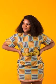 アフロの髪型を持つ若いアフリカ系アメリカ人の女の子。コピースペースと黄色の壁の肖像画。