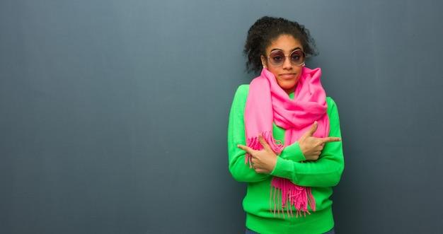 青い目をした若いアフリカ系アメリカ人の女の子は、2つのオプションのどちらかを決定します