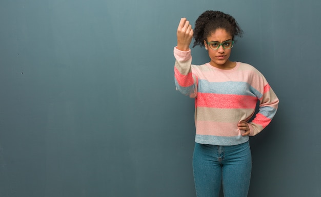 Young african american girl with blue eyes doing a typical italian gesture