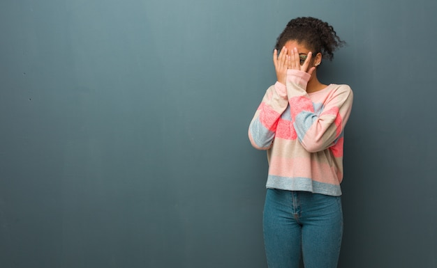Young african american girl with blue eyes feels worried and scared