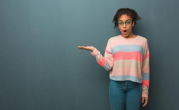 손바닥 손에 뭔가 들고 파란 눈을 가진 젊은 아프리카 계 미국인 여자