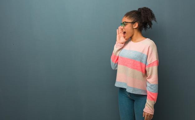 Молодая афроамериканская девушка с голубыми глазами шепчет сплетни подтекст