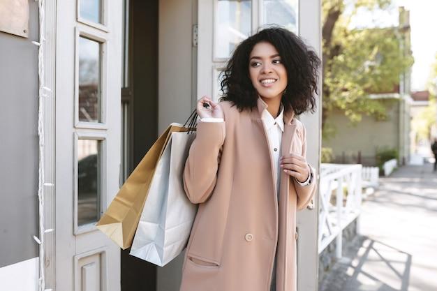 Молодая афро-американская девушка с темными вьющимися волосами, стоящая у двери довольно улыбающаяся девушка в бежевом пальто, стоящая с пакетами в руке портрет красивой дамы с хозяйственными сумками
