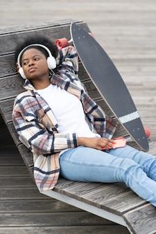 헤드폰을 끼고 야외에서 스케이트보드를 탄 젊은 흑인 소녀는 음악을 듣습니다.