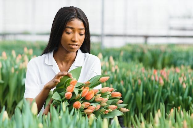 Молодая афро-американская девушка, рабочий с цветами в теплице.