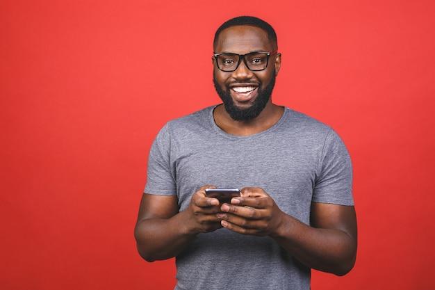 Молодой афро-американский парень, одетый в повседневную отправку и получение сообщений