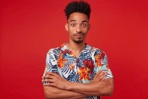 Молодой афроамериканец в гавайской рубашке, недоуменно глядя в камеру, стоит на красном фоне со скрещенными руками.