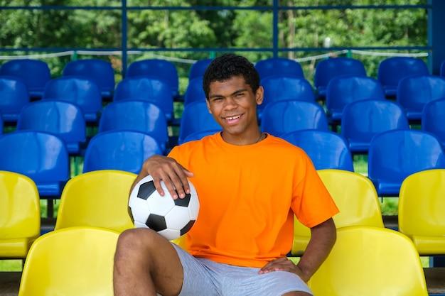 여름에 야외 텅 빈 축구 관중석에 축구공을 들고 있는 젊은 아프리카계 미국인 남자