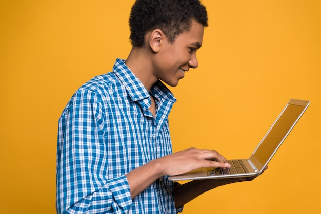 Young african american guy works with laptop.