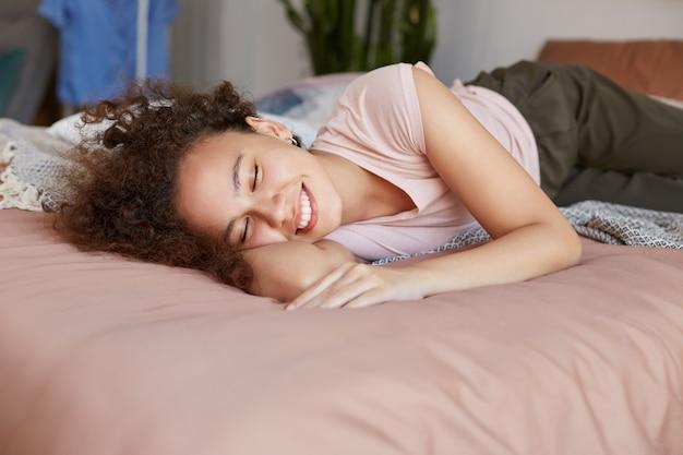 침대에 누워있는 젊은 아프리카 계 미국인 행복한 아가씨는 닫힌 눈으로 광범위하게 웃고 집에서 맑은 아침을 즐길 수 있습니다.