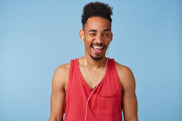 Young african american happy man looks and winks, listens a new song of a popular group, wears in a red jersey, stands.