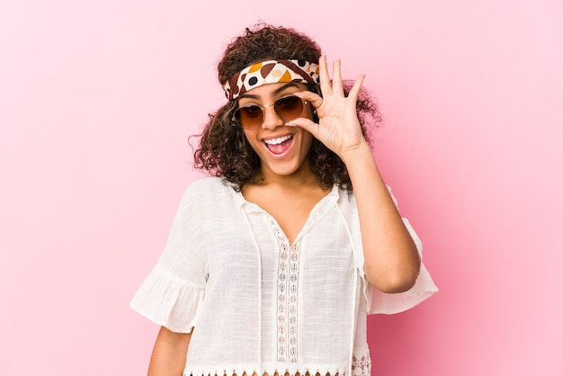 ピンクに分離された若いアフリカ系アメリカ人の流行に敏感な女性は目にokのしぐさを維持して興奮しています。