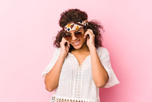 Молодая афро-американская хипстерская женщина, изолированная на розовых стенах, заволакивающих уши руками.