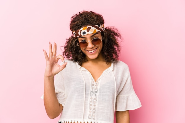 Young african american hipster woman isolated on pink wall cheerful and confident showing ok gesture.