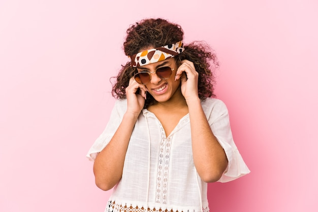 Young african american hipster woman isolated on pink wall covering ears with hands.