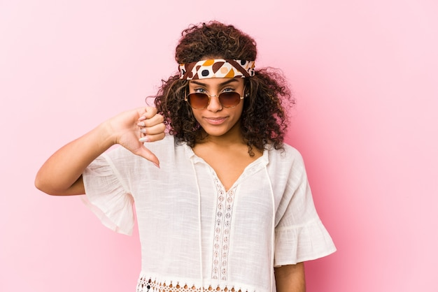 Young african american hipster woman isolated on pink wall showing a dislike gesture, thumbs down. disagreement concept.