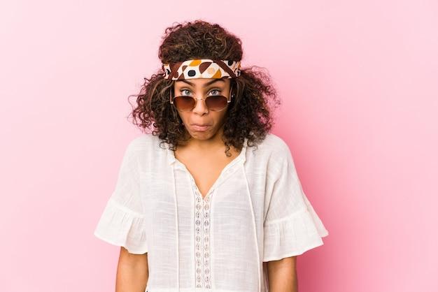 Молодая афро-американская женщина битника на розовой стене пожимает плечами и смущает открытые глаза.