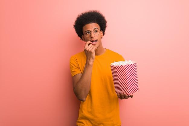 ポップコーンのバケツを持っている若いアフリカ系アメリカ人は、コピースペースを見ている何かについて考えてリラックスしました